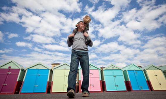 Father carries his son on his shoulders in front of beach huts